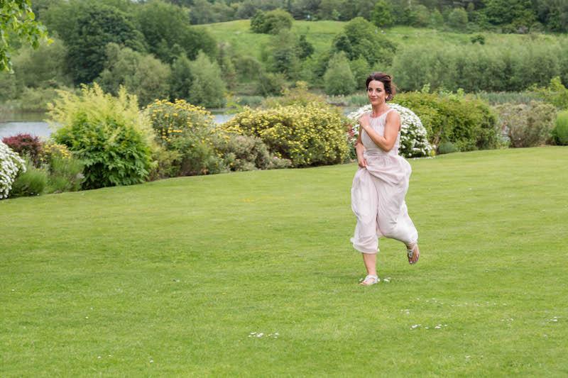 Bridesmaid running across grass