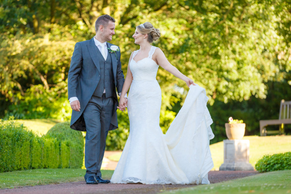 Bride and groom walk and laugh in Yorkshire wedding