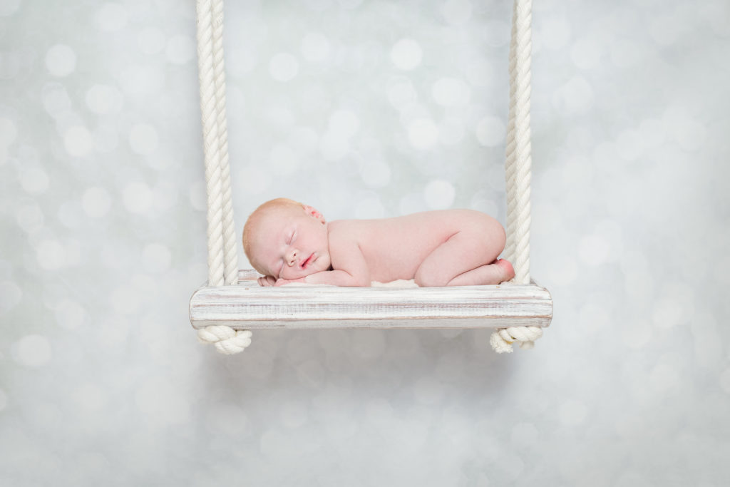 Newborn baby posed on a swing in a studio photoshoot