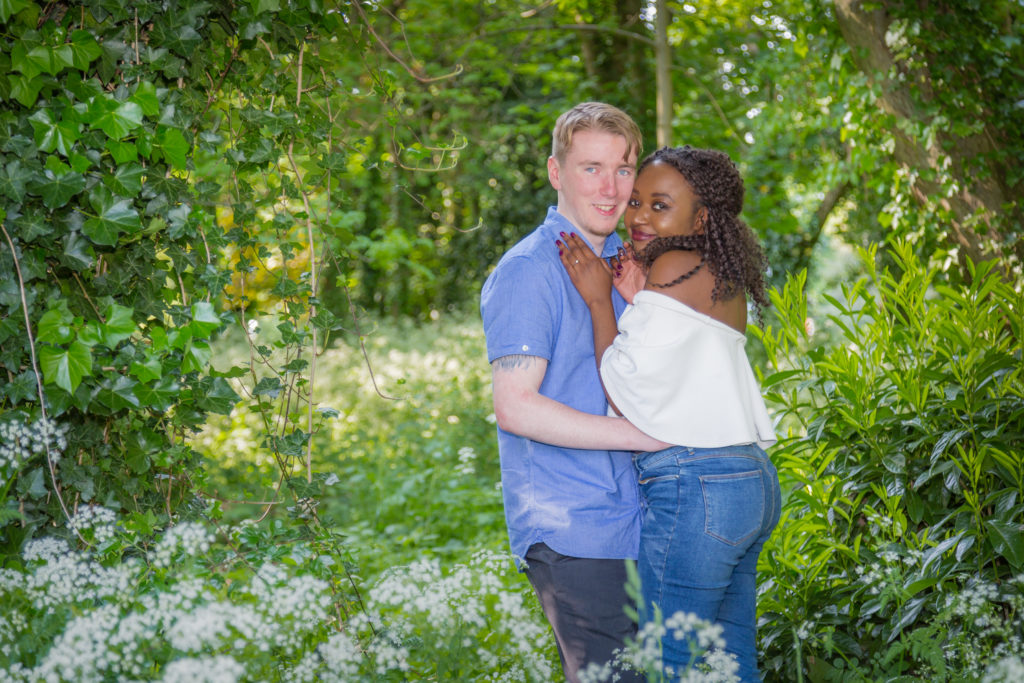 Couple cuddling in woodland setting for engagement photoshoot in West Yorkshire