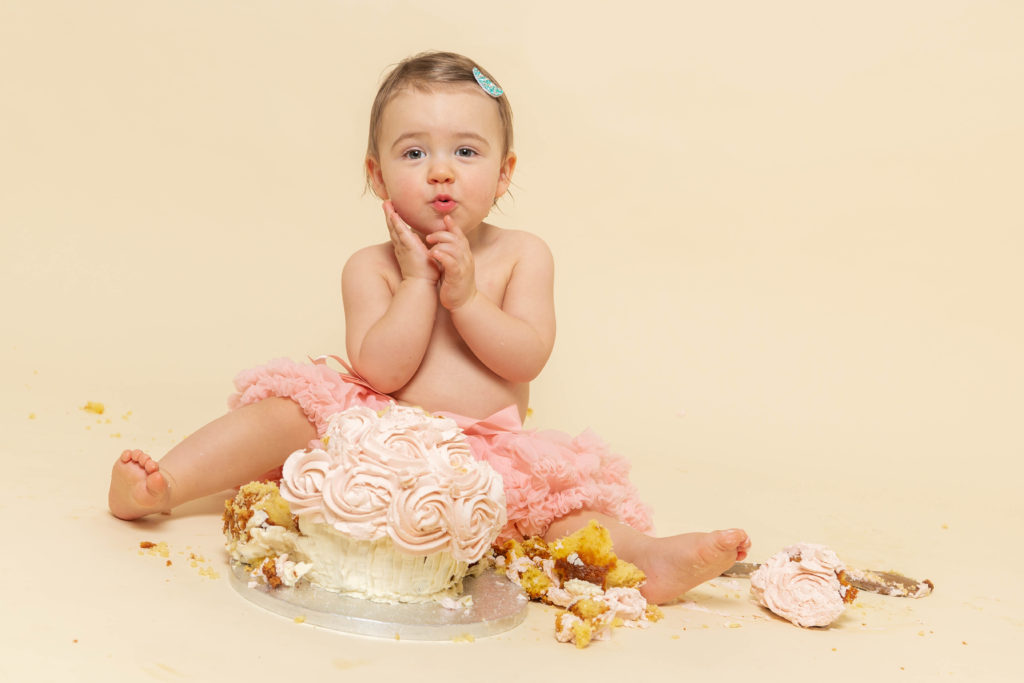 Baby girl sitting in a smashed birthday cake