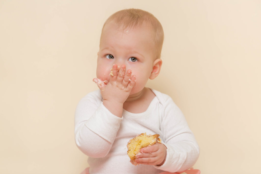 Baby eating cake during a cake smash photoshoot in west Yorkshire