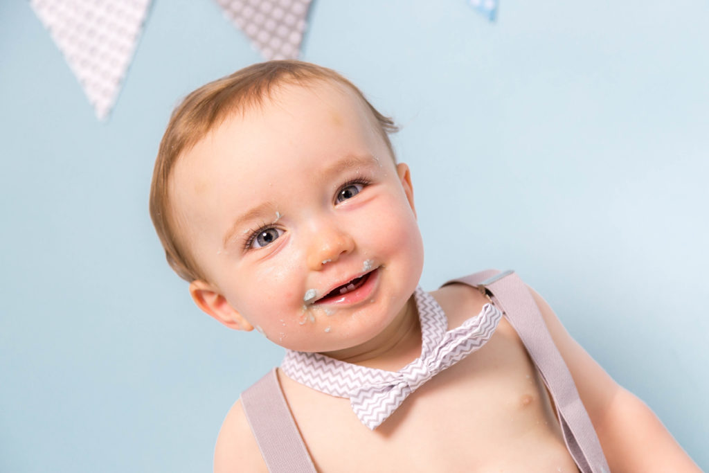 Smiling baby wearing a bow tie during a photoshoot in West Yorkshire