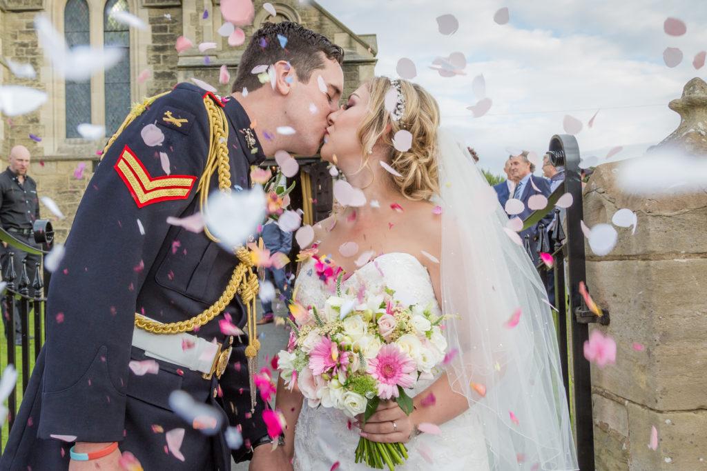 Soldier kisses his bride under confetti