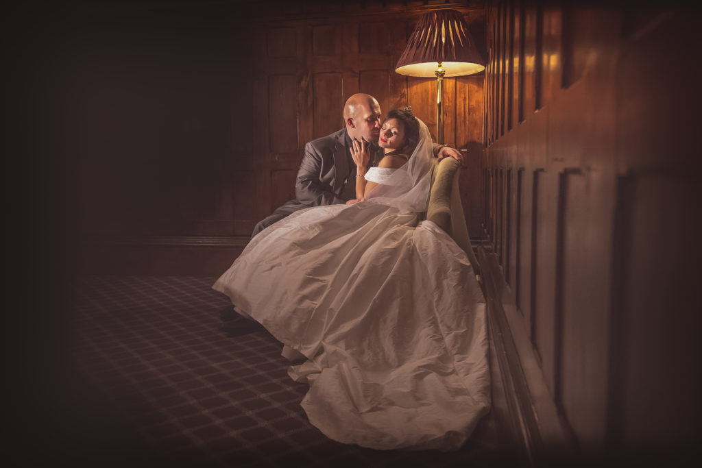 Glamourous photo of a bride and groom cuddling in soft lighting indoors by Sarah Hargreaves of Sugar Photography