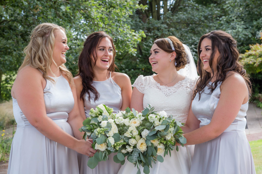 Bride and bridesmaids laugh during a wedding at Waterton Park in West Yorkshire