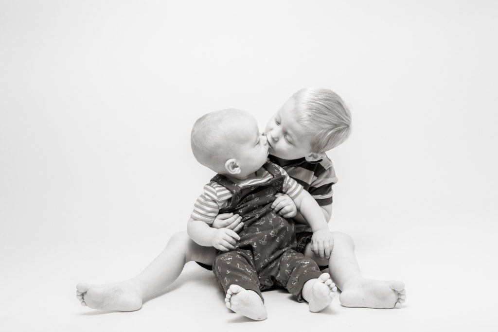Brothers kissing during a photoshoot in west Yorkshire