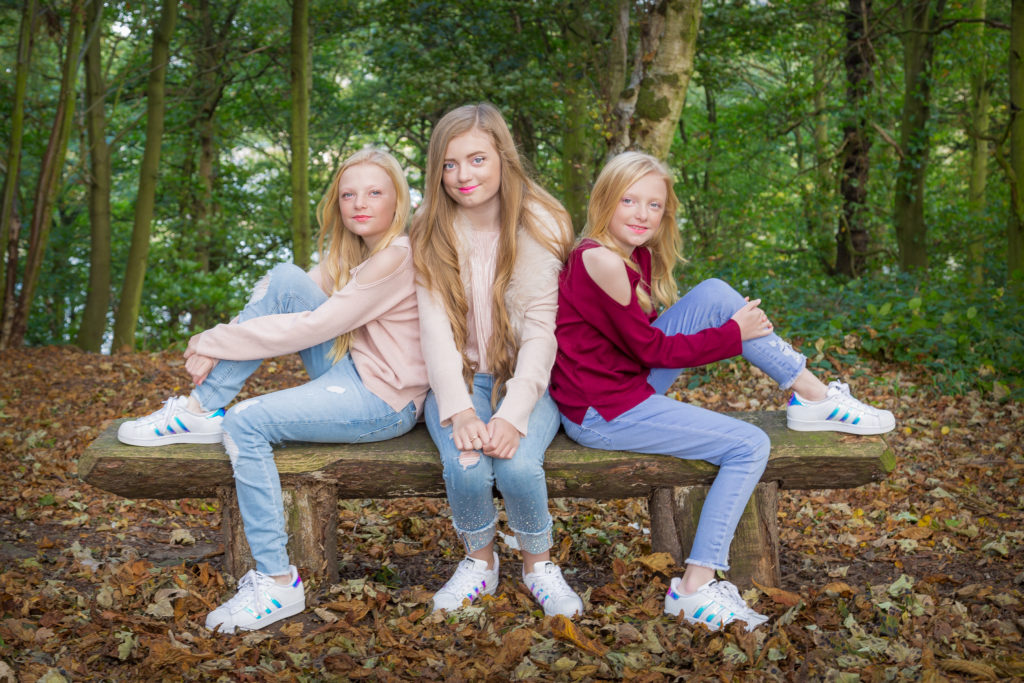 Three girls pose on a woodland bench in a photoshoot in west yorkshire