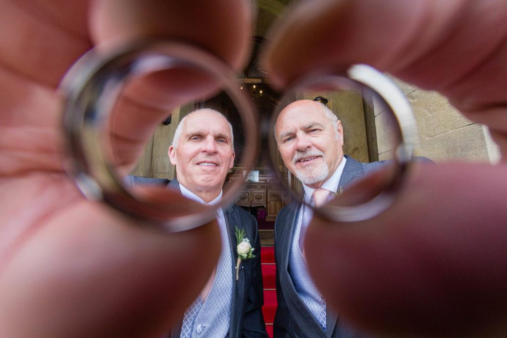 Groomsmen hold wedding rings to camera lens