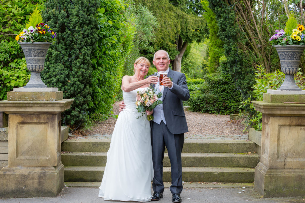 Bride and Groom sharing a drink in the sunshine