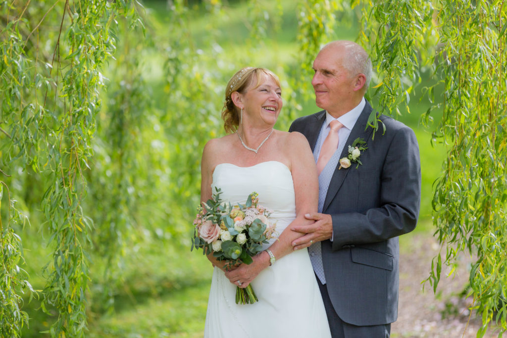Mr and Mrs Darbyshire laugh in the gardens