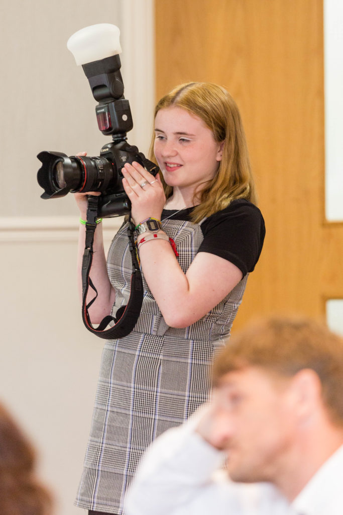 A young girl holds a camera
