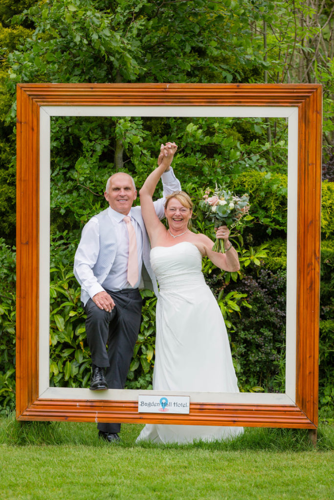 Bride and groom pose with large picture frame